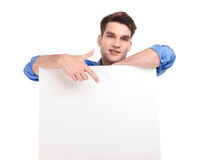 Handsome man pointing his finger to a white board. Royalty Free Stock Image