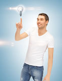 Handsome man pointing at light bulb Stock Images