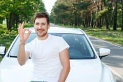 Handsome man pointing ok near car Stock Photos