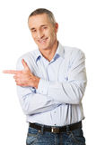 Handsome man pointing to the left Stock Images