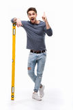 Handsome man pointing up and holding building level isolated on white Royalty Free Stock Image