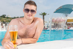 Handsome Man in the Pool with a Glass of Beer Royalty Free Stock Photography