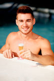 Handsome man in the pool toasting with champagne Stock Photos