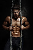 Handsome man posing. Handsome bodybuilder posing naked with chains, looking at camera Stock Images