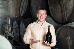 Handsome man posing with bottle of wine. In winery cellar Stock Photography