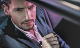 Handsome man posing in the limousine Stock Photography