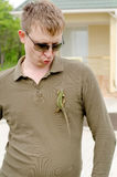 Handsome man posing with a lizard on his shirt Stock Image