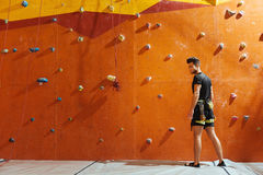 Handsome man posing near climbing wall. Male sport. Handsome young confident man posing near climbing wall while standing in climbing gym and preparing to mount Stock Image