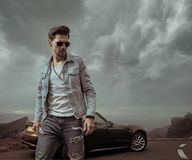 Handsome man posing next to the luxurious convertible car. Handsome guy posing next to the luxurious convertible car royalty free stock photo