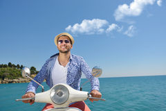 Handsome man posing on a scooter in a vacation context. Street fashion and style. Stock Image