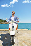 Handsome man posing on a scooter in a vacation context. Street fashion and style. Royalty Free Stock Photography