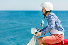 Handsome man posing on a scooter in a vacation context. Street fashion and style. Stock Images