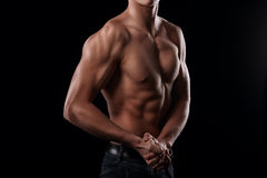 Handsome man posing and showing his arm muscles. While posing on black background Royalty Free Stock Photography