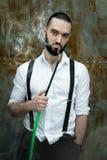 Handsome man posing in white shirt smoking hookah Stock Photography