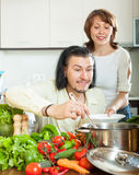 Handsome man and positive woman with vegetables in the kitchen Royalty Free Stock Photo