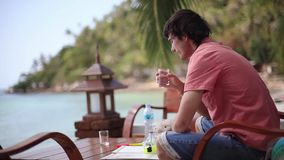 Handsome man pouring and drinking water in cafe on a beach. 1920x1080. Hd stock video footage
