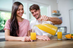 Handsome man pouring orange juice in a glass Royalty Free Stock Photography