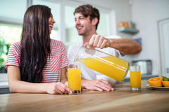 Handsome man pouring orange juice in a glass Royalty Free Stock Photo