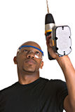 Handsome man with power drill. Handsome African-American repairman uses power drill stock photography