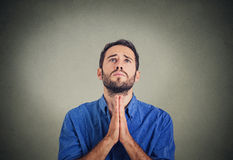 Handsome man praying hands clasped hoping for best asking for forgiveness stock photography