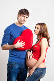 Handsome man and pregnant woman with red heart Royalty Free Stock Photos
