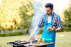 Handsome man preparing barbecue Stock Photos