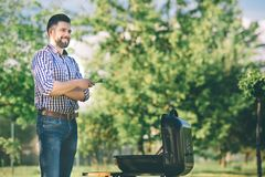 Handsome man preparing barbecue for friends. man cooking meat on barbecue - Chef putting some sausages and pepperoni on. Handsome men preparing barbecue for stock photography