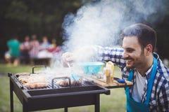 Handsome man preparing barbecue Stock Images