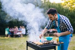 Handsome man preparing barbecue Royalty Free Stock Images