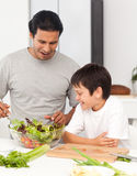 Handsome man preparing a salad with his son Royalty Free Stock Images