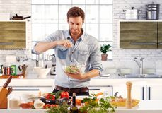 Handsome man preparing salad in kitchen Stock Photo