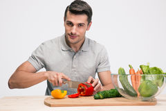 Handsome man preparing salad Stock Images