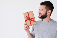 Handsome man with present box looking sideward Stock Images