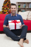 Handsome man with present at home Stock Images