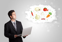 Handsome man presenting a cloud of healthy nutritional vegetable Stock Photography