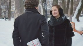 Handsome man presents the gift to the woman in winter park stock footage