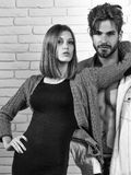 Handsome man and pretty girl. Young couple of handsome men or muscular macho in unzipped jacket with pretty cute girl or beautiful women in knitted coat on white Royalty Free Stock Photo