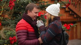 Handsome Man and Pretty Woman Drinking Coffee on Tradition Christmas Market. Wife and Husband Look at Each Other with. Love and Tenderness Having Hot Drink stock video footage