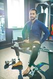 Handsome man with prosthetic leg sitting on sport bench. Content confident handsome young bearded man with prosthetic leg sitting on sport bench and looking at stock photography