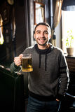 Handsome man in a pub or bar holding mug the beer high in the air for cheers Royalty Free Stock Photos