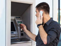 Handsome man put his credit card at the atm Stock Photography