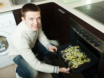 Handsome man putting fish  into oven at  kitchen Royalty Free Stock Photo