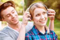 Handsome man putting headphones on pretty girl Royalty Free Stock Photography