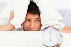 Handsome man putting his head under the pillow Royalty Free Stock Photos