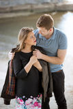 Handsome man putting jacket on girlfriends shoulders at riverban Royalty Free Stock Image