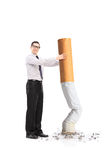 Handsome man putting out a huge cigarette Royalty Free Stock Images
