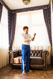 Handsome man putting on shirt standing near window at his room in morning. New opportunities, dating, wedding day or. Handsome man putting on shirt standing near Stock Photo