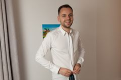 Handsome man putting on shirt standing near window at his room i Stock Photo