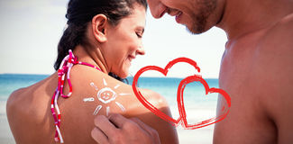 handsome man putting sun tan lotion on his girlfriend Stock Images
