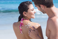Handsome man putting sun tan lotion on his girlfriend Royalty Free Stock Images